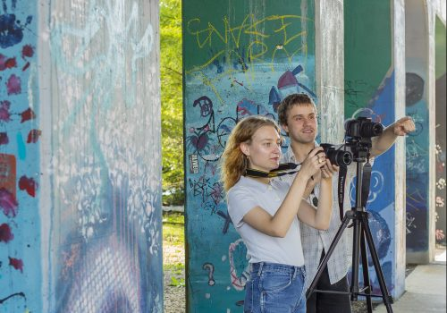 Students in front of graffiti art with cameras